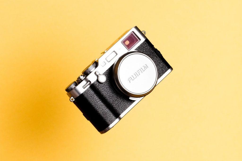 Foto van een fototoestel met een gele achtergrond.