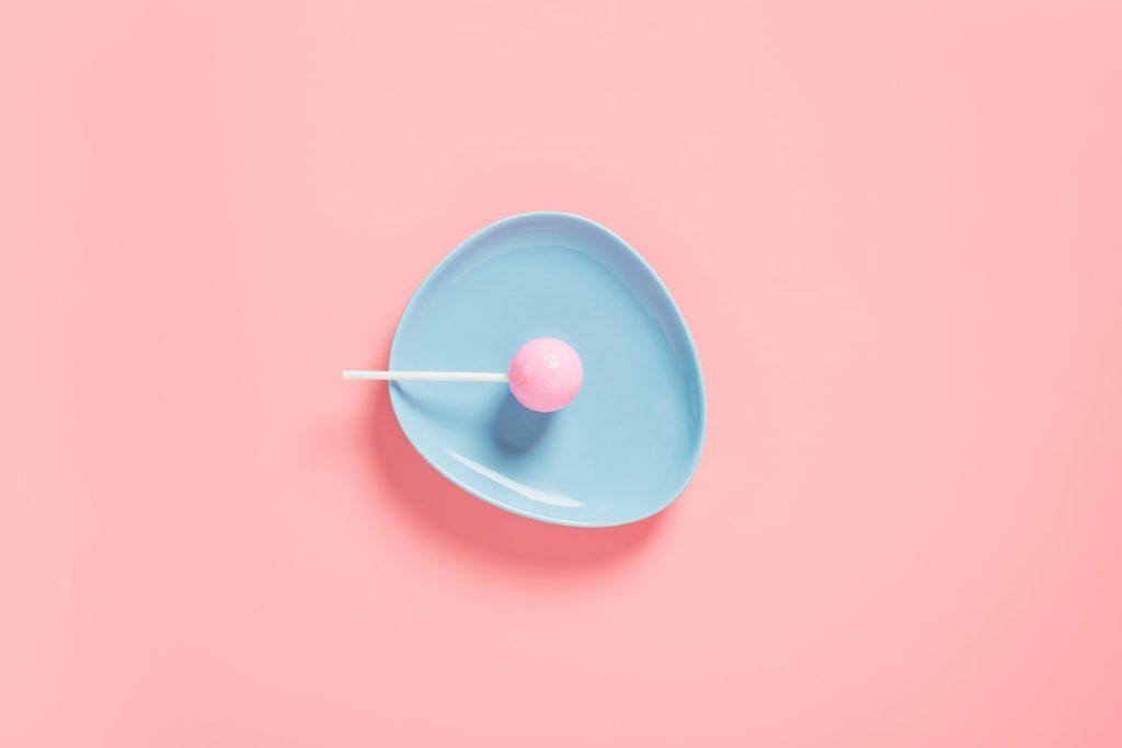 Foto van een roze lolly op een blauw bordje met roze achtergrond